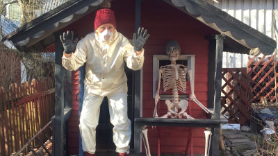 Kvinna i skyddsutrustning och ett skelett framför en lekstuga.