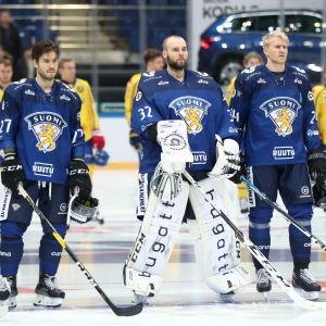 Oula Palve, Rasmus Tirronen och Niklas Friman lyssnar på nationalsången.