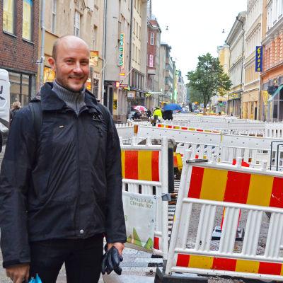 Tomas Palmgren vid byggstängsel på gata.