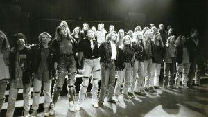 Ungdomar i en musikal står rad på scenen.