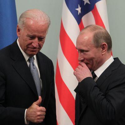 Biden ja Putin seisovat mustissa puvuissa Yhdysvaltain lipun edessä. Putin hymyilee ja pitää kättään leuan ja suunsa edessä. Biden näyttää oikealla kädellään peukaloa.