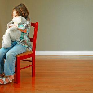 Ett ensamt barn kramar ett mjukisdjur.