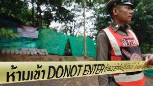 """Ett avspärrningsband med texten """"Do not enter"""" och en vakt vid området kring Tham Luang-grottorna."""