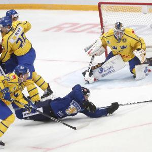 Jani Lajunen vräker sig mot mål i en ishockeymatch mellan Finland och Sverige.