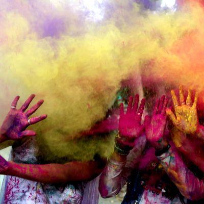 Värijauhepilven keskeltä näkyy käsiä