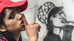 Sonita poserar framför en vägg med graffiti.