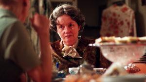 Liisamaija Laaksonen istuu pöydässä päässään harmaa peruukki. Elokuvasta Liian paksu perhoseksi.