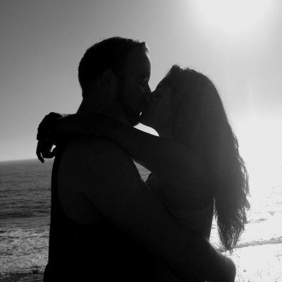 En man och en kvinna kysser varandra på en strand, svartvit