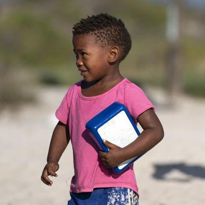 Sydafrikanska barn kommer för att hämta mat.