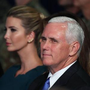 Mike Pence står framför Ivanka Trump.