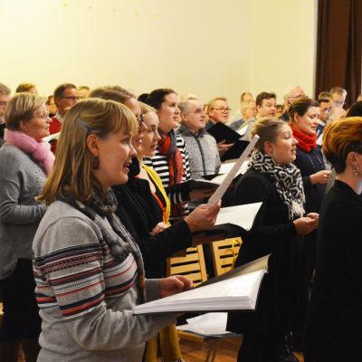Flera kvinnor och män i en stor sal. De håller i nothäften och sjunger.