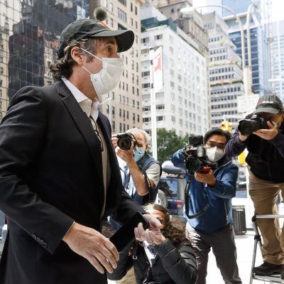 Michael Cohen kasvosuojuksessa kuvaajien edessä.