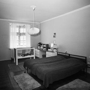Mustavalkoinen kuva 1960-luvun kerrostalon makuuhuoneesta
