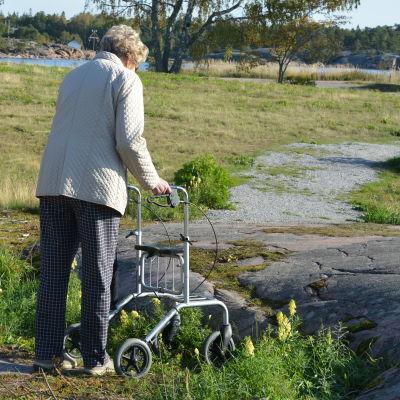 Dorrit Söderblom står med en rullator vid en klippa. Lisbet Tuominen står till vänster.