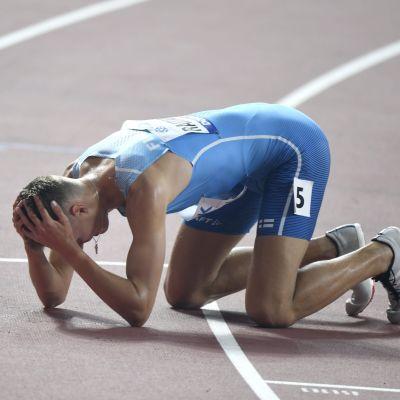 Topi Raitanen ligger på knäna på löpbanan.
