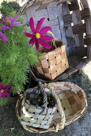 Olika spånkorgar staplade i och bredvid varandra. Blommor syns också bredvid korgarna.