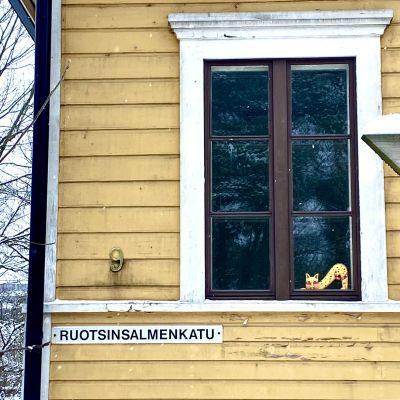 Närbild på gul trähusvägg mot vintrig bakgrund. I fönstret finns en bild på en gul katt som sträcker på sig. Under fönstret står det Ruotsinsalmenkatu och siffran 9.