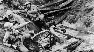 Sotilaita kuraisessa kranaatinkuopassa elokuvassa Kunnian polut, Kirk Douglas lähinnä kameraa