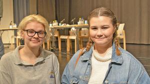 Två unga kvinnor står framför en scen.