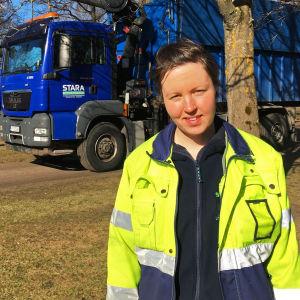 Carla Hakala i arbetskläder framför Staras lastbil.