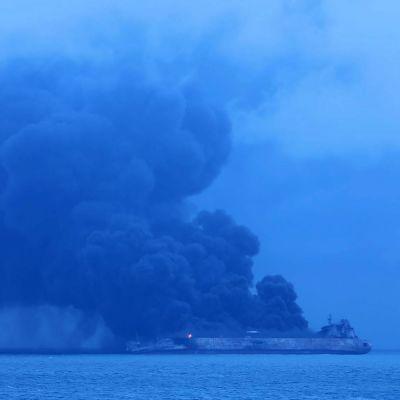Tankfartyg brinner på havet utanför Shanghai. Tjock svart rök stiger från båten.
