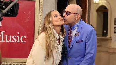 En kvinna i beige jacka blir pussad av en man i klarblå kostym.