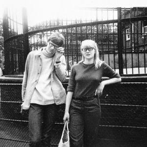 Mustavalkoisessa kuvassa nuori mies ja nainen nojaavat aitaan Lontoossa 1960-luvulla