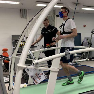 Tapani Laakso juoksee juoksumatolla hengityskaasuanalysaattori kasvoillaan.