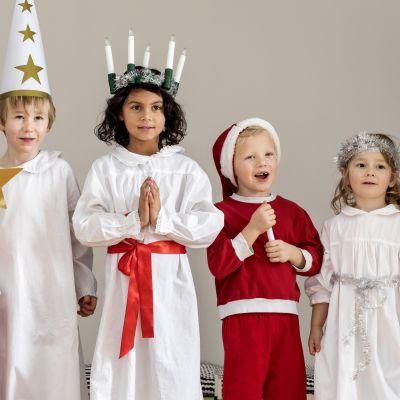 Jouluasuisia lapsia: tonttuja, enkeli, tiernapoika ja Lucia-neito.