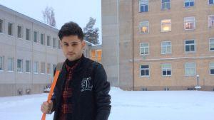 En ung man står framför en stor stenbyggnad, det snöar.