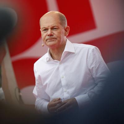 Olaf Scholz i en vit skjorta. Han tittar framåt.