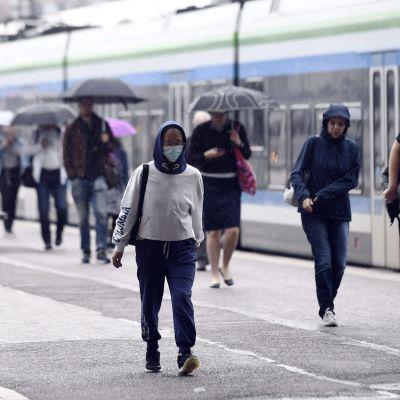 Personer på Helsingfors järnvägsstation en regnig dag i augusti.