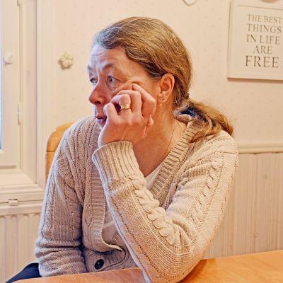 Sari Riutta istuu keittiön pöydän ääressä.