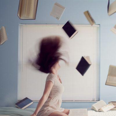 En kvinna på en säng med en drös böcker uppkastade i luften. Symbol för stress.