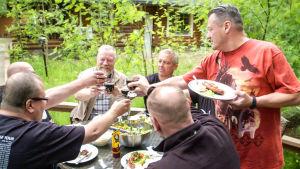 Kuusi miestä vehreällä mökkipihalla kohottavat maljat.