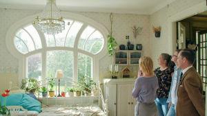 Interiör där fyra personer betraktar ett stort fönster.