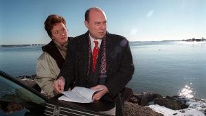 Mies ja nainen meren rannalla, aurinkoinen kevätsää. Mies selaa papereita, molemmat synkän oloisia.