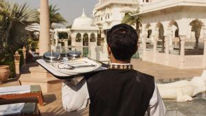 Tarjoilija pitää kädessään olkansa päällä tarjotinta. Kuvattu selän takaa. Edessä näkyy Taj Mahal.