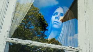Kvinna tittar ut genom fönster med orolig min.
