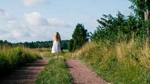 Kvinna i klänning går längs sandstig med ryggen vänd mot tittaren.