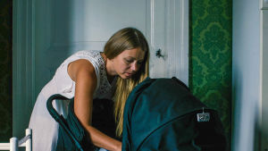 Kvinna pysslar om barn i barnvagn inne i sitt hem.