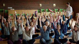 Yogande kvinnor sträcker upp händerna mot taket.