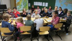 Salapoliisikerholaisia pöydän ääressä luokassa.