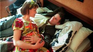 Mies ja nainen makaavat sängyllä. Nainen on raskaana.