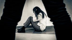 En rädd kvinna syns sitta på golvet mellan en mans ben.
