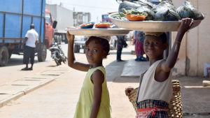 Två minderåriga flickor som bär stora fat med varor på huvudet.