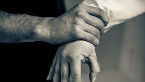 en manlig hand håller hårt on en kvinnas hand
