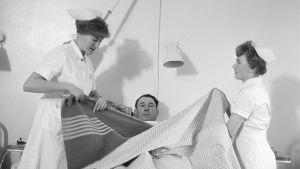 Två sjuksköterskor vårdar en manlig patient.