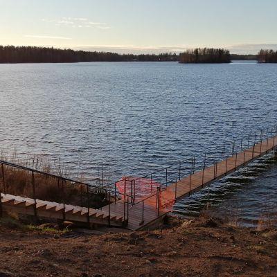 Pitkä laituri järvessä iltaruskon aikaan.