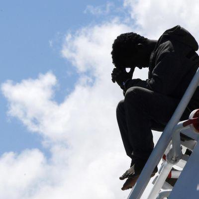 En man väntar på att få stiga i land från räddningsfartyget Rio Segura i hamnen i Salerno 29.6.2017